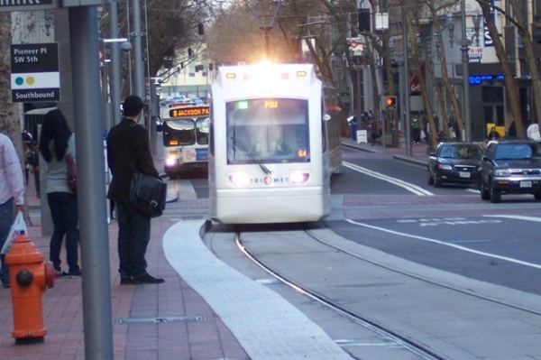 LRT train on Portland's 5th Ave. transit mall swings to the curbside station to pick up waiting passengers. Photo: L. Henry.