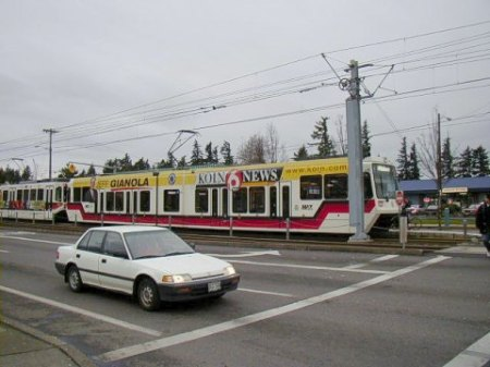 Light rail train in East Burnside St. approaches intersection and station at NE 181st. Ave. Photo: Adam Benjamin.
