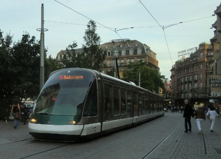 As evening approaches, a tram glides through Strasbourg's Place Kléber as pedestrians stroll along the other track. Photo: Franz Roski.
