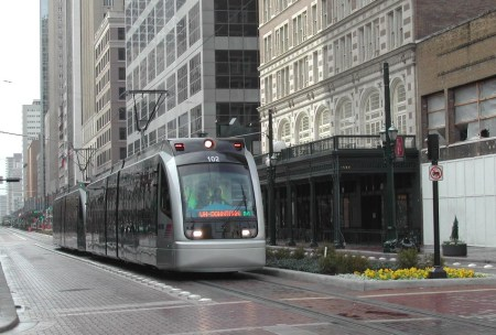 Two-car Houston MetroRail light rail train glides northbound in reservation along Main St. Notice landscaping in median, where station platforms are also placed. Photo: Mike Harrington.
