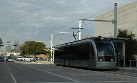 Having crossed intersection, Houston LRT train accesses station on Fannin St. as traffic control system allows queue of motor vehicles to make left turn over track reservation behind it.