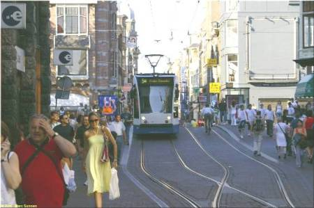 Another photo showing crowds of pedestrians, an approaching tram, and a clearview of a transition from double-track to interlaced track. (Photo: Marc Sonnen.)