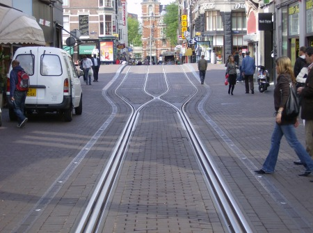 Focus on interlaced track construction in the Leidsestraat. Notice how the two tracks  Notice how the two tracks virtually merge to form what almost seems like a single track — but there are separate parallel rails for each direction, laid next to each other. Also, only one rail in each direction actually cross each other (this type of passive, stationary rail crossing is called a frog).
