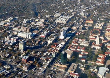 """Aerial view (looking north) of """"Drag"""" section of Guadalupe St. (wide arterial running from bottom middle of photo to upper right). Western edge of UT campus is at far right, and extremely dense West Campus neighborhood occupies middle left of photo. In upper right corner, Guadalupe jogs northwest, then north again; main travel corridor eventually merges with North Lamar further north. Photo: Romil, posted in forum.skyscraperpage.com."""