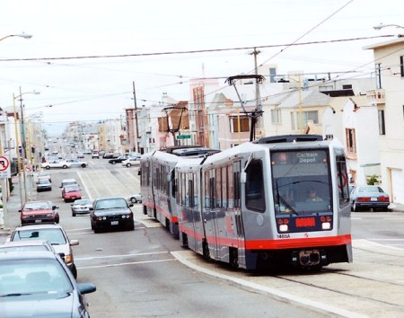 N-Judah Line Muni Metro light rail transit (LRT) train running in raised median on San Francisco's Judah St. Alignment in this constricted 80-foot-wide arterial includes space for 2 dedicated light rail tracks, 4 vehicle lanes, and shared sidewalk for pedestrians and bicyclists. Similar alignment design could fit dedicated LRT tracks, 4 traffic lanes, and sidewalks into Austin's Guadalupe-Lamar corridor. Photo (copyright) Eric Haas.