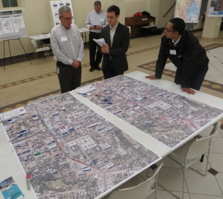 At Dec. 3rd Guadalupe Transportation Corridor Project public event, project manager Alan Hughes (center, in checkered shirt) discusses project issues over table with Drag corridor maps. At far right in photo is Roberto Gonzalez of Capital Metro's Planning Department. Photo: L. Henry.
