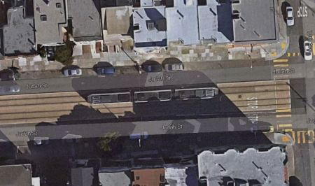 Aerial view of Judah St. corridor segment, showing central reservation with Muni Metro LRT train, motor vehicle lanes on each side, and sidewalks on each side of arterial. Photo: Google Maps Satellite View.
