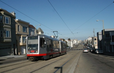 In this view of single-car train on slightly raised median near 16th Avenue, transverse spanwire that holds OCS power wire can be seen behind train, suspended between TES poles on either side of street. TES poles also serve as street light masts, a typical dual function. PHOTO: Peter Ehrlich.