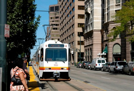 Denver: Passengers waiting to board LRT train running in curbside lane on Stout St. Photo: Peter Ehrlich.