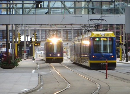 Two light rail trains pass on 5th St., a major downtown east-west thoroughfare with dedicated lanes for light rail. Photo: L. Henry.