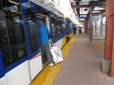 Traveler with baggage boards Blue Line train at downtown station. With level boarding (station platform level with car floor), carrying on luggage is easy. Photo: L. Henry.