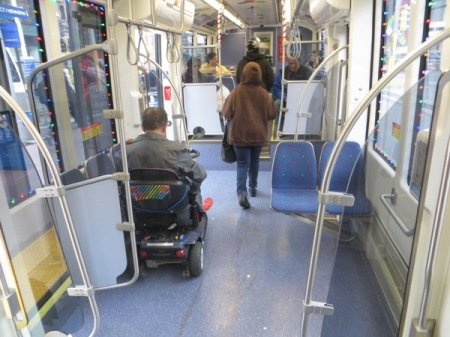 Passenger in wheelchair easily maneuvers chair into accessible space aboard car. In contrast to buses — no tiedowns, no operator assistance needed, no passengers ousted from their seats!  Photo: L. Henry.